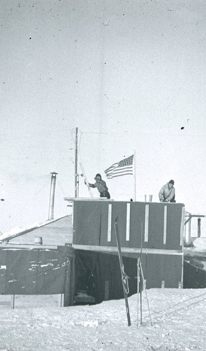 Two men on building roof in wind