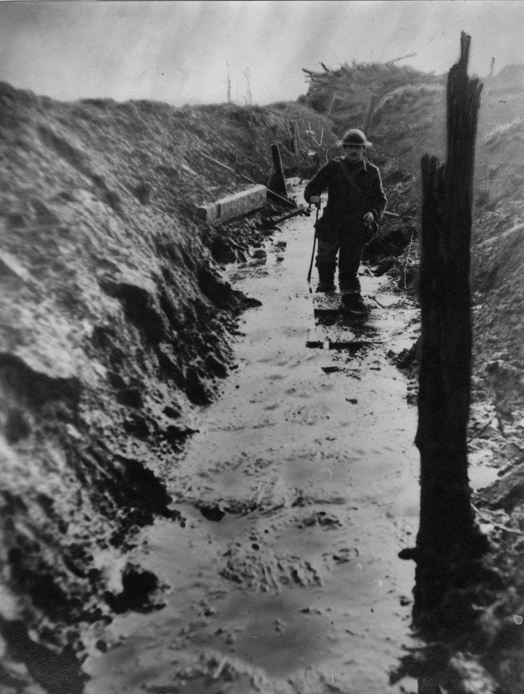 Walking knee deep in slimy mud along a communication trench at La Basse Ville, forward of Messines, in Belgium.