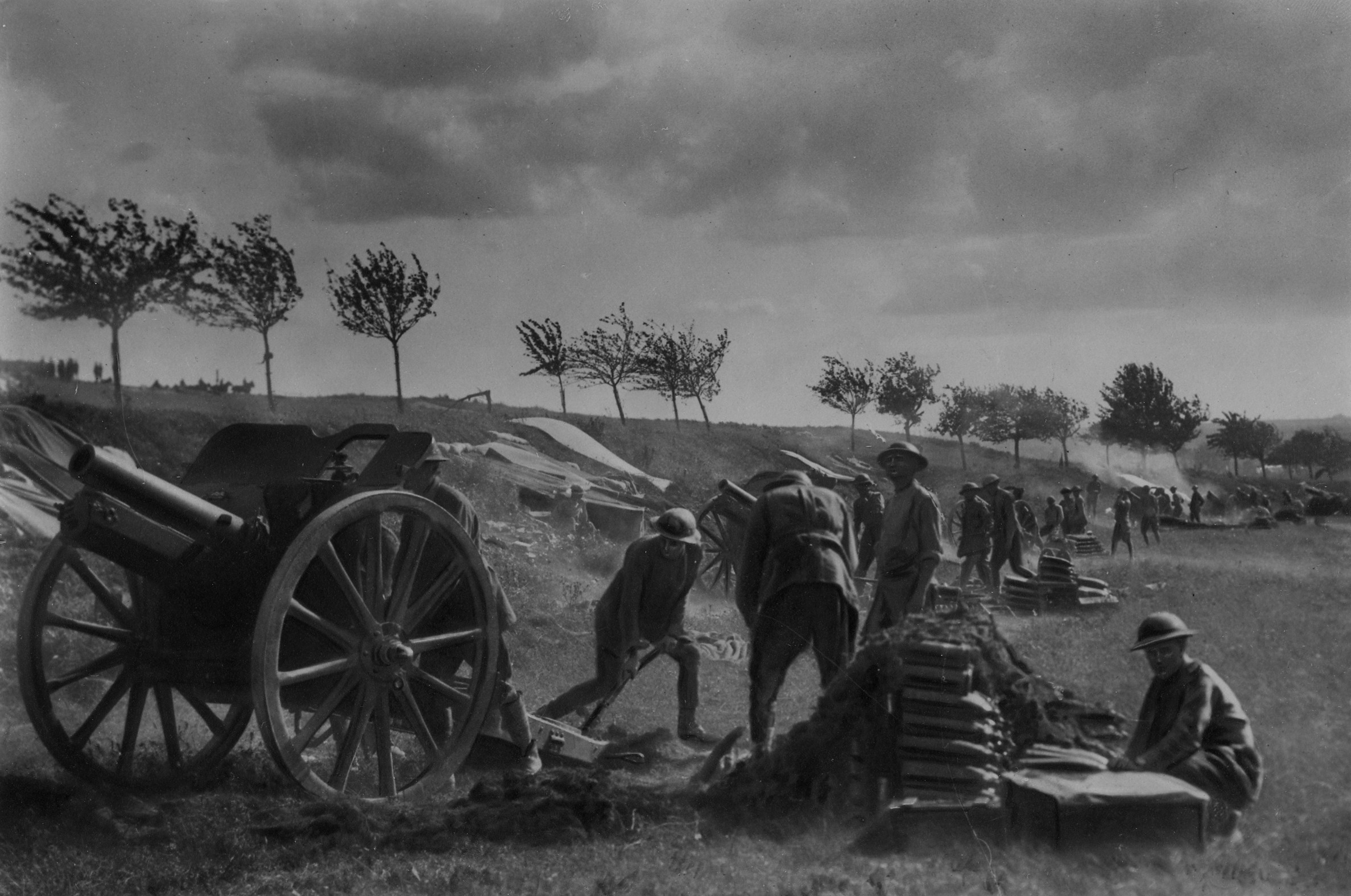Members of the New Zealand Field Artillery Battery in action a few minutes after taking up their new position at Grevillers during the Battle of Amiens on 8 August. Note the shells stacked on the ground.