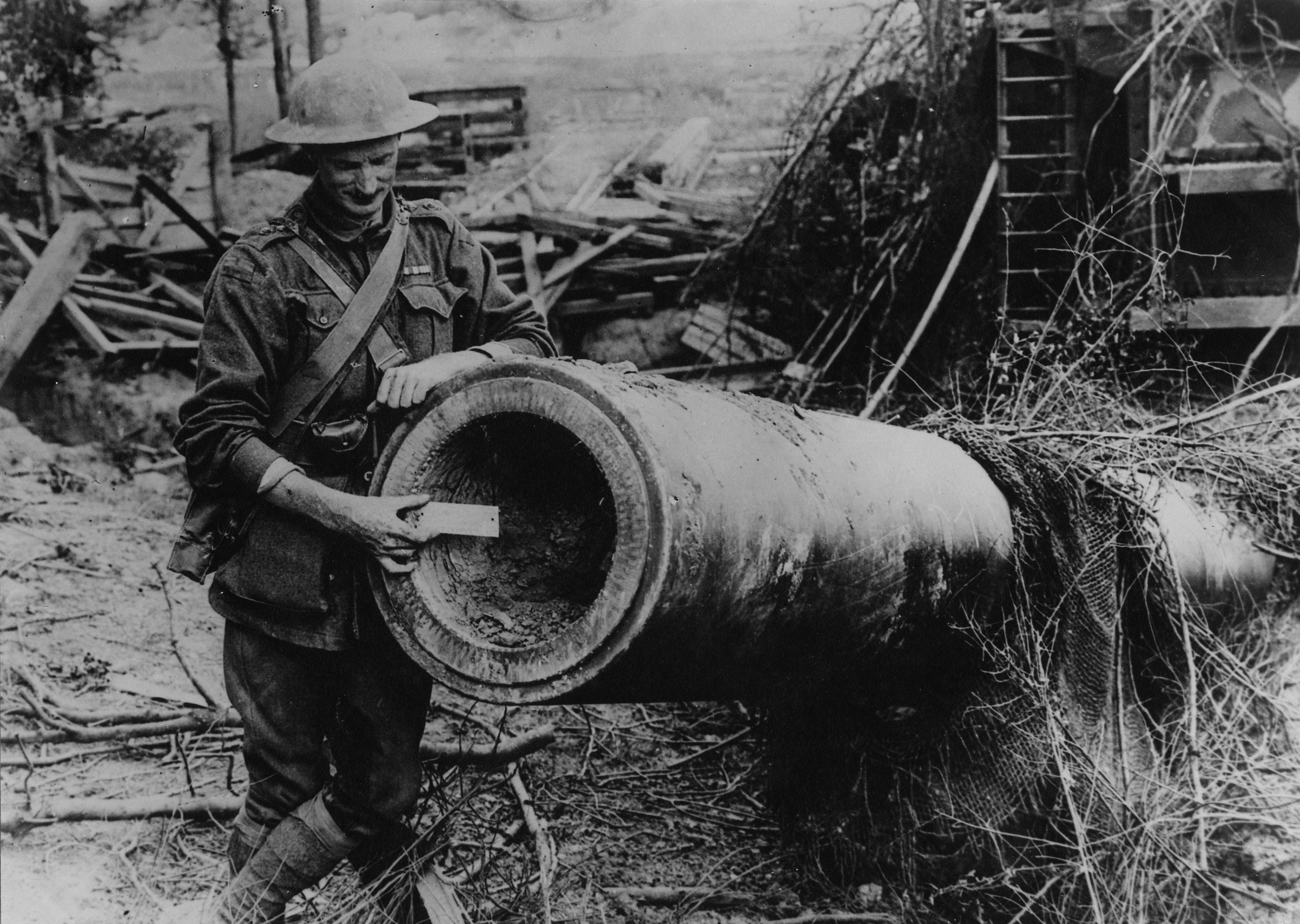Lieutenant C. O. Clark MC MM, Intelligence Officer of the 3rd Battalion, with a 6 inch rule inset in the muzzle of the wrecked 15 inch naval gun taken by the Australian troops in a bayonet attack, at Arcy Wood, near Chuignolles, on 23 August 1918.