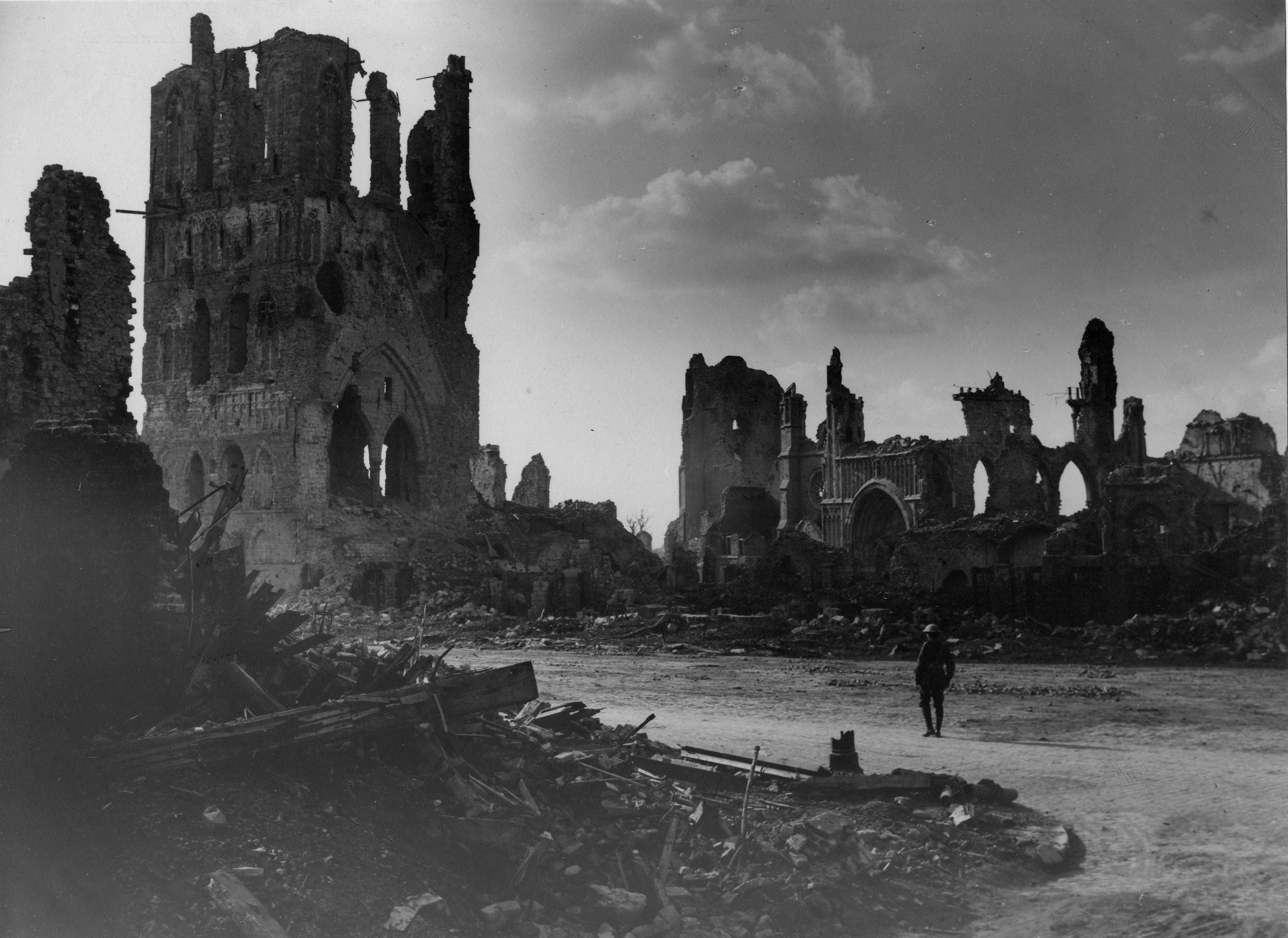 An unidentified Austrailan soldier standing amidst the ruins of Ypres, Belgium, and looking towards the remains of the Cloth Hall.