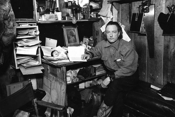 Admiral Byrd at his workstation reading a book