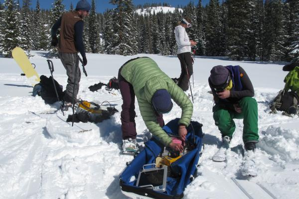 Team of Scientists Assembling Equipment on a Sled