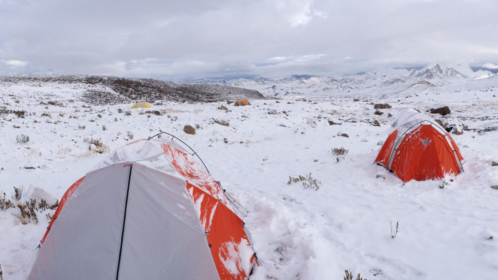 Tents in snow-covered terrain with mountains in background